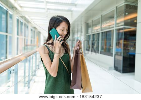 Woman holding shopping bag and talk to cellphone