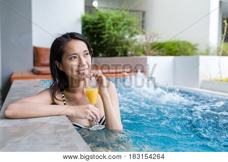 Woman in jacuzzi pool and enjoy drink