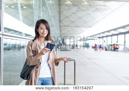 Woman using cellphone with her luggage in airport