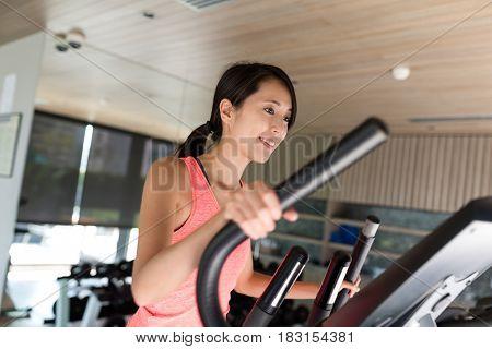 Sport Woman training on Elliptical machine