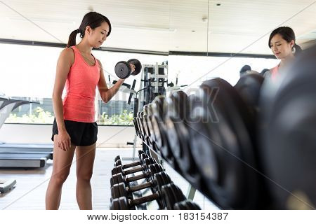 Woman practices lifting weights in gym