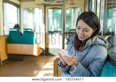 Woman sending sms on cellphone on train