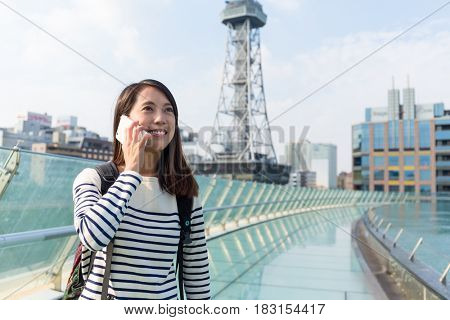 Woman talk to cellphone in japanese city