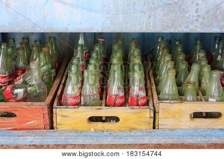Alte, verstaubte vintage Coke-Flaschen in alten Holzkisten