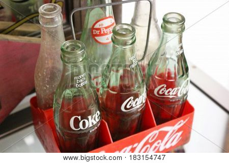 Alte, verstaubte vintage Coke-Flaschen in einer Kiste