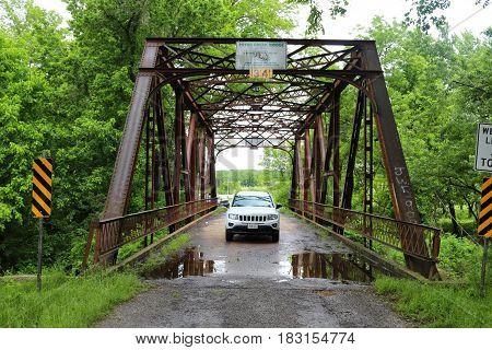 Ein Jeep unter einer Brücke, umgeben von Bäumen