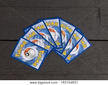 BEVERWIJK THE NETHERLANDS - April 23 2017: Several very popular Pokemon cards on dark wooden background