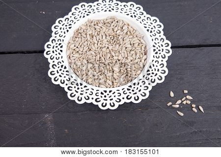 Sunflower seeds in white bowl on wooden background