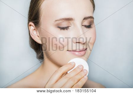 Portrait with face of young blonde beautiful girl with nude make up and with cotton pad in her hand, smiling with closed eyes and posing on white background