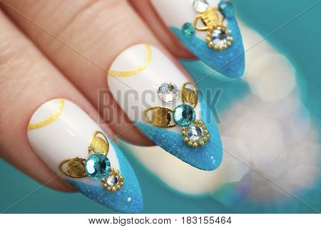 Luxurious glamorous sandy blue French manicure with rhinestones boulongne and gold plated women's nails closeup.