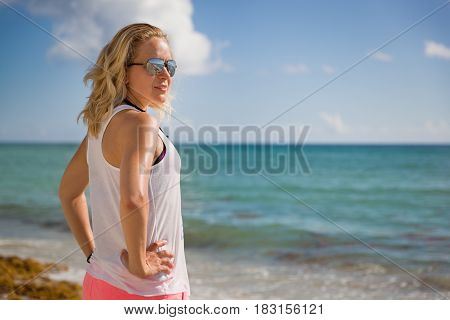 Young sportive woman in sun glasses standing on the beach and looking into distance. Vacations by the sea. Summer camp. Girl relaxing after work out outdoors.