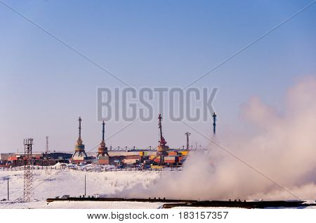 construction cranes on production in the foreground puffs of vapor from water cooling