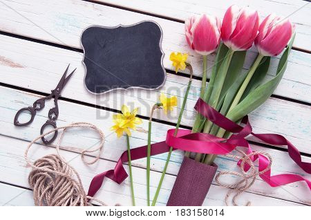 Spring tulips with small empty blackboard sign