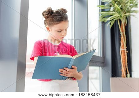 Concentrated Little Girl Standing Near Window And Reading Book