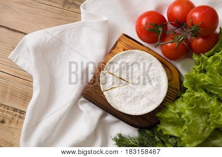 Top view on Camembert cheese on wooden board with tomatoes and green salad. Serving French homemade soft cheese. Food concept