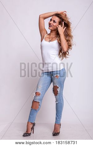 Happy beautiful woman in jeans and white shirt on studio background