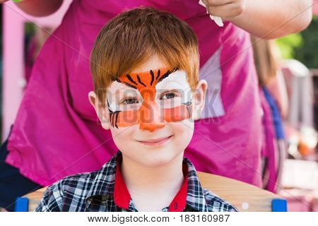 Face art at children holiday, tiger painting on boy's face