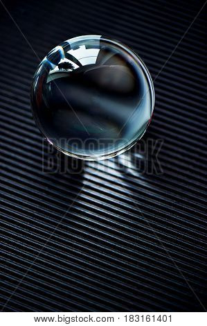 Glass globe or drop of water on a dark graphite corrugated paper . Clean and Shine