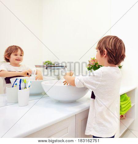 Cute Kid Washing Hand Under Tap Water In Bathroom