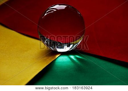 Glass globe or drop of water on a background of yellow, red and green velvet paper.Clean and Shine