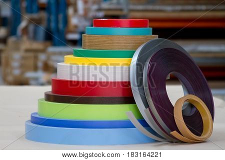 Furniture accessories. Multicolored bobbins of PVC edge and melanin for the manufacture of furniture. Lie pyramid.