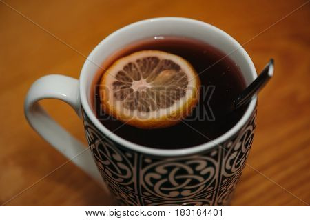 Mug of tea with a slice of lemon close up. Cozy atmosphere. Home treatment maintenance of health. Vitamin C.