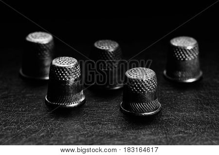 A few old thimbles on a black background. Monochrome.