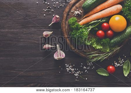 Desk with fresh organic vegetables and greens on wood background. Healthy natural food abundance on rustic wooden table with copy space. Cooking ingredients top view, soft toning