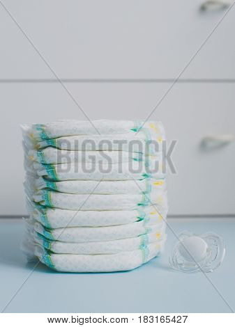 A stack of diapers against a white wardrobe. Vertically