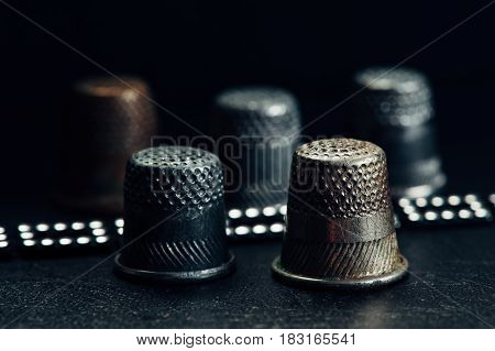 A few old thimbles on a black background. Brilliant bracelet.