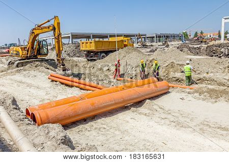 Zrenjanin, Vojvodina, Serbia - May 30, 2015: Embed water pipes in trench on building site. Big excavator is excavating soil at construction site project in progress.