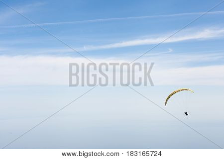 Skydiver plans against the blue and white sky