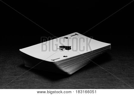 A deck of cards on a black background. The ACE of spades. Monochrome.