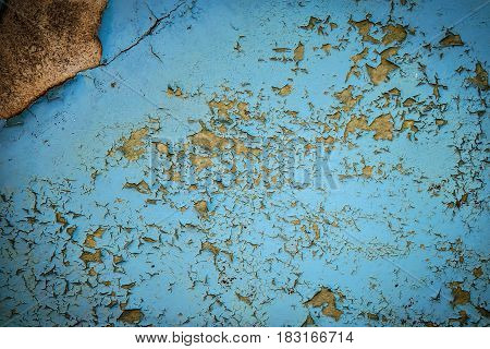 Grunge background of old cracked blue paint on the wall