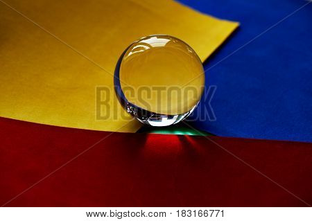 Glass globe or drop of water on a background of green, red and blue velvet paper.Clean and Shine