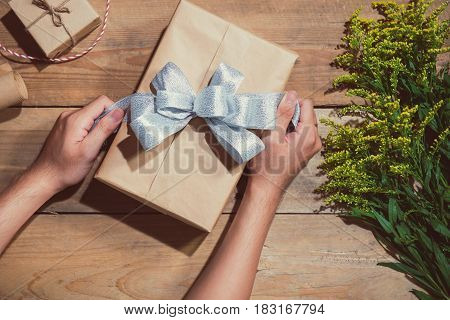Hands wrapping gift box on wooden table. View from above.