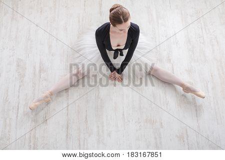Classical Ballet dancer. Beautiful graceful ballerine in tutu skirt sit on floor in ballet class, top view
