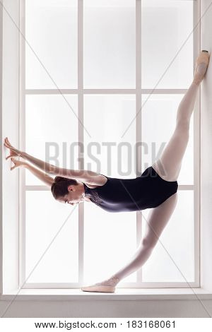 Ballerina show standing split at window sill background. Classical ballet training