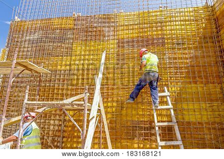 Construction worker is binding rebar for tall reinforced concrete construction at the building site.