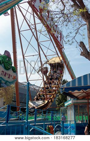 Tel Aviv Israel April 16 2016 : Visitors to the city's attractions park ride on the swing ride in Tel Aviv Israel