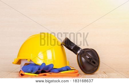 Standard construction safety , helmet, glove, ear cushions on wooden background