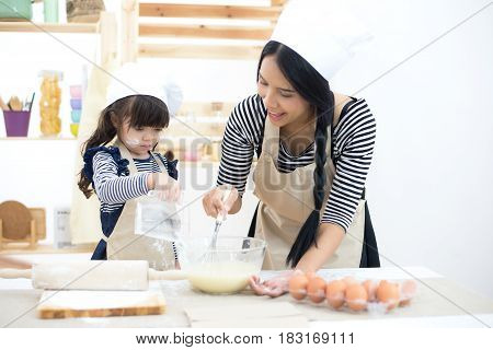 Mother and child daughter girl are cooking cookies and having fun in the kitchen.
