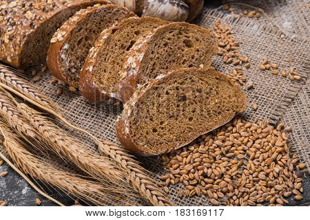 Plenty of sliced bread background. Bakery and grocery concept. Fresh, healthy whole grain sliced rye loaf, sprinkled flour on sackcloth and rustic wood table, food closeup.