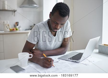 Portrait of dark-skinned man sitting at kitchen table filling application form writting something on papers managing with utility bills calculating expences trying to solve budget problems