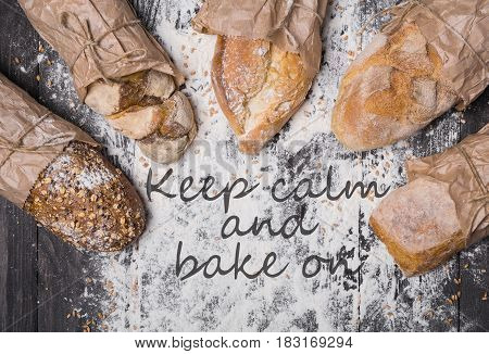 Cooking concept background. Keep calm and bake text, different bread sorts, wrapped in craft paper top view with copy space in the middle on wooden table, sprinkled with flour. Soft toning