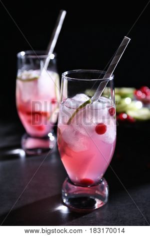 Refreshing cocktails with cranberry on dark table