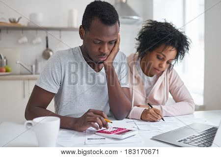 Unhappy african male sitting at kitchen making calculations and his wife filling in papers. Young couple having big trouble while calculating domestic budget frustrated with amount of expenses