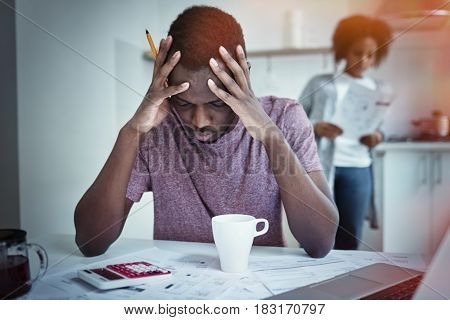 Young african american husband sitting at kitchen table with papers touching head with both hands feeling devastated not able to pay bills because of debts his wife standing in background