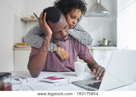 African-american female hugging her unemployed husband while he looking at laptop using online banking with frustrated expression not able to pay off utility bills. Financial problems concept