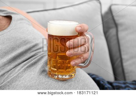 Man holding glass of beer on his big belly, closeup